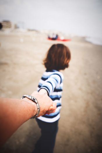 Father holding hand of son on beach