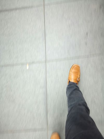 Low Section Of Man Wearing Leather Shoes Walking On Footpath