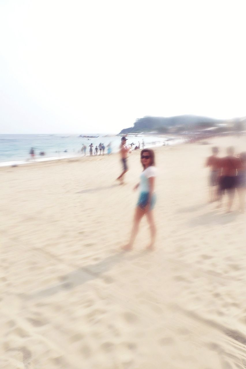 BLURRED MOTION OF PEOPLE WALKING ON BEACH