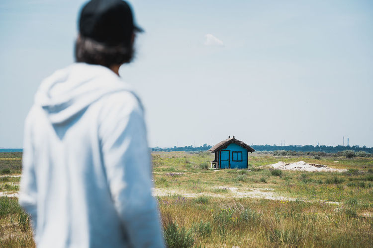 Rear view of man standing on field by the beach against blue house and sky
