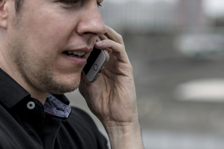 Close up profile of a man talking on a phone. The lower part of the face is visible. Adult Afternoon Man Mobile Phone Profile Shallow Depth Of Field Casual Clothing Caucasian Ethnicity Cell Phone  Close Up Day Electronics  Golf Shirt Good Looking Hand Handsome Jaw Lower Face Male Mouth Open One Person Phone Portable Information Device Summer Talking On Phone