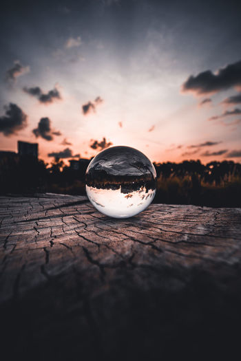 Close-up of crystal ball on water against sky during sunset