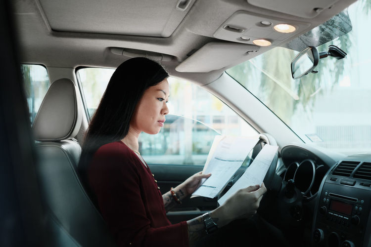 Side view of woman holding documents while sitting in car
