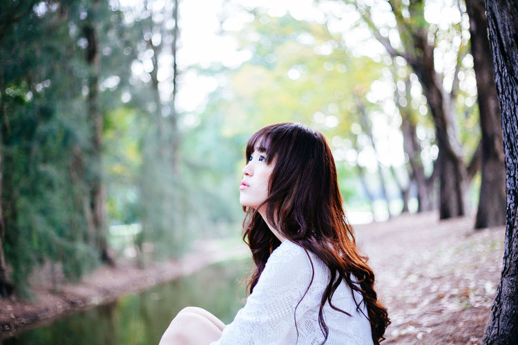 Beauty in White Dress One Person Tree Long Hair Real People Hairstyle Forest Focus On Foreground Leisure Activity Side View Lifestyles Hair Plant Young Adult Land Casual Clothing Day Portrait Looking Women Outdoors Contemplation Beautiful Woman Teenager
