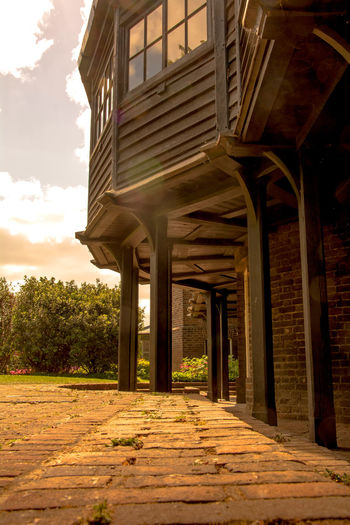 Architectural Column Architecture Brick Pavement Brown Company Low Perspective No People Oil Industry Old House Outdoors Piles Piles Of Wood Sky Spice Garden Treehouse Wood - Material Wood And Glass Wooden Building Wooden Columns