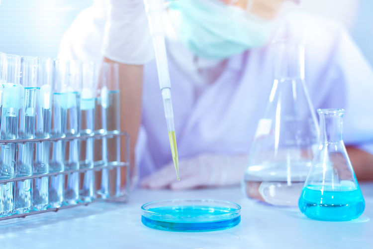 Scientist examining blue chemical in laboratory