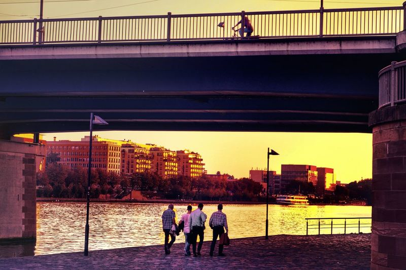 End Of The Working Day Four Men Walking Home Along The River Bank  Under The Bridge Houses In The Sunset Light The Golden Hour architecture River Water Building Exterior Bridge - Man Made Structure Bridge City Frankfurt Am Main Germany🇩🇪 Enjoy The New Normal