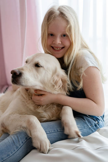 Portrait of smiling girl with dog at home