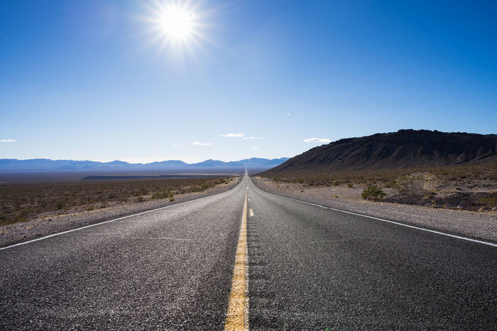 One of the endless roads between Nevada and California. Asphalt Blue Blue Sky California Clear Sky Desert Desert Endless Endless Road Freedom Landscape Mountain Nature Nevada No People Outdoors Road Scenics Sky Straight Straight Ahead Sun Sunlight The Way Forward Travel
