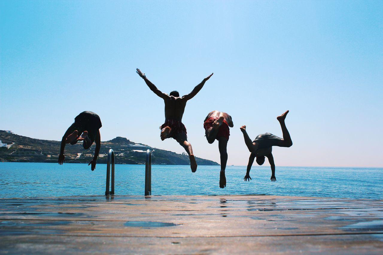 MEN JUMPING IN SWIMMING POOL AGAINST SEA