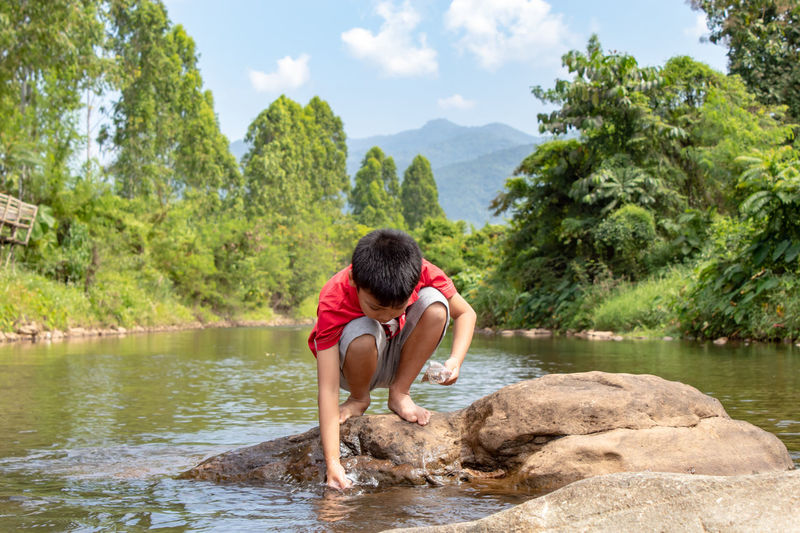 Boy crouching on rock in river against sky