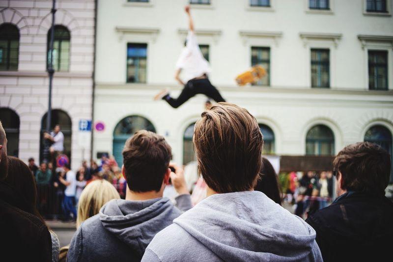 Spectators looking at man performing stunt on street