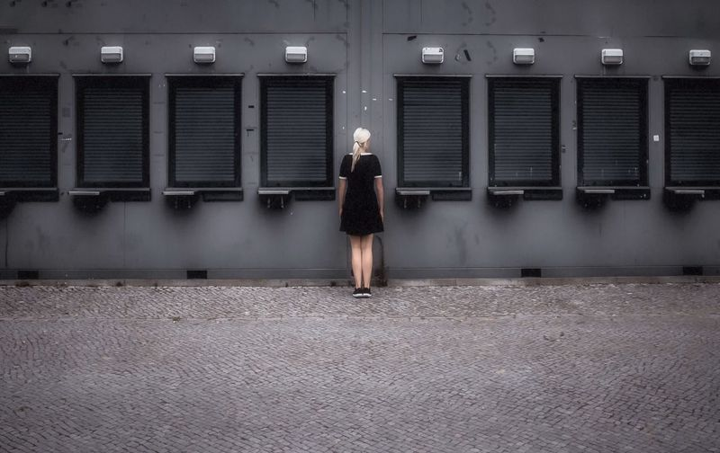 Rear view of woman standing amidst shutters on wall