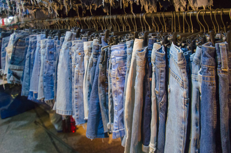 Close-up of denims hanging for sale at clothing store