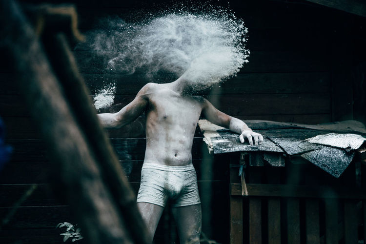 Hopeless shirtless man standing by powder in abandoned house