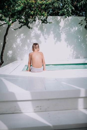 Rear view of shirtless man sitting in swimming pool