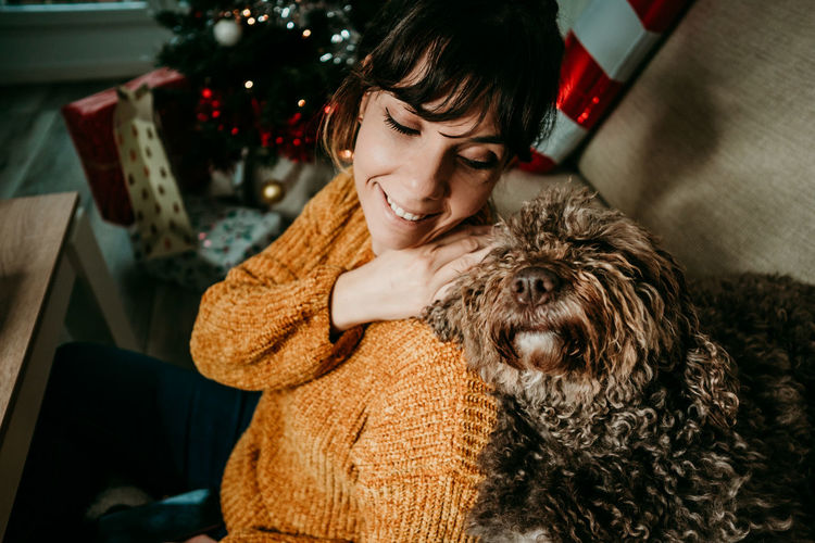 Smiling woman sitting with dog at sofa