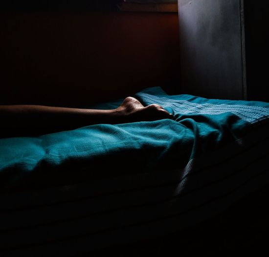 Low section of person sleeping on bed in darkroom