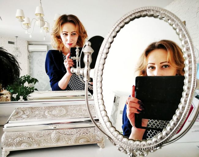 Portrait Of Mid Adult Woman Reflecting On Various Mirrors At Home