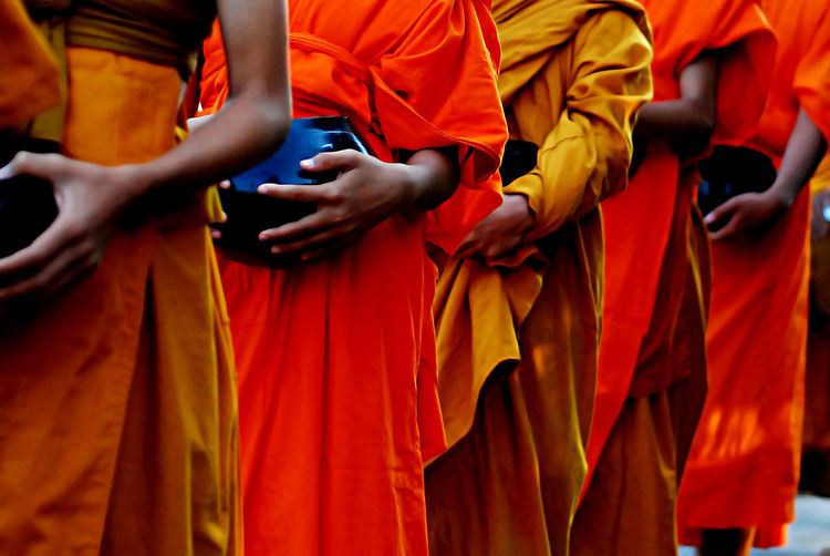 Midsection of monks wearing traditional clothing while standing in row