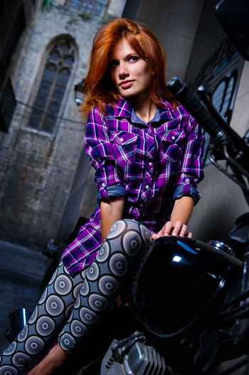 Low Angle View Of Young Woman Sitting On Motorcycle By Building