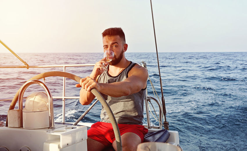 Sea Water Transportation Nautical Vessel One Person Leisure Activity Mode Of Transportation Real People Sky Three Quarter Length Smiling Sailing Travel Men Emotion Happiness Holiday Nature Sailboat Yacht Horizon Over Water Outdoors Luxury Yachting Bearded Man Captain Summer Blue Sea Sunlight Adult Candid