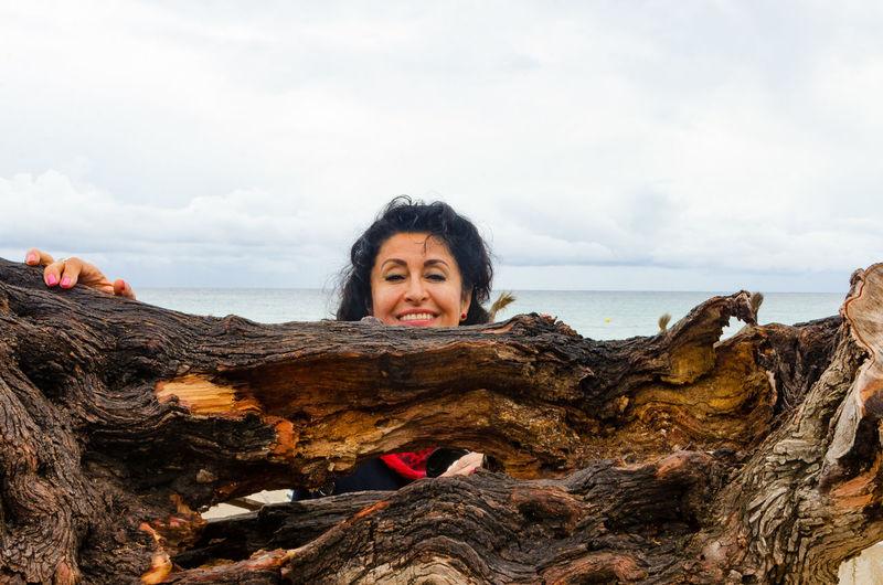 Close-up portrait of woman against drift wood
