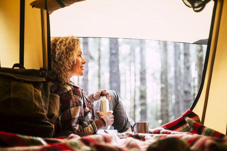 Woman sitting by tent with coffee cup in forest