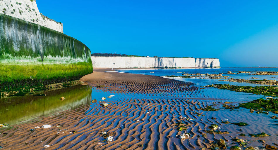 View of white cliffs and beach in Kingsgate Bay, Margate, East Kent, UK Chalk Cliffs Margate Architecture Beach Blue Building Exterior Built Structure Clear Sky Copy Space Day Kingsgate Bay Land Low Tide Nature No People Reflection Sand Scenics - Nature Sea Sky Sunlight Tranquility Water White Cliffs