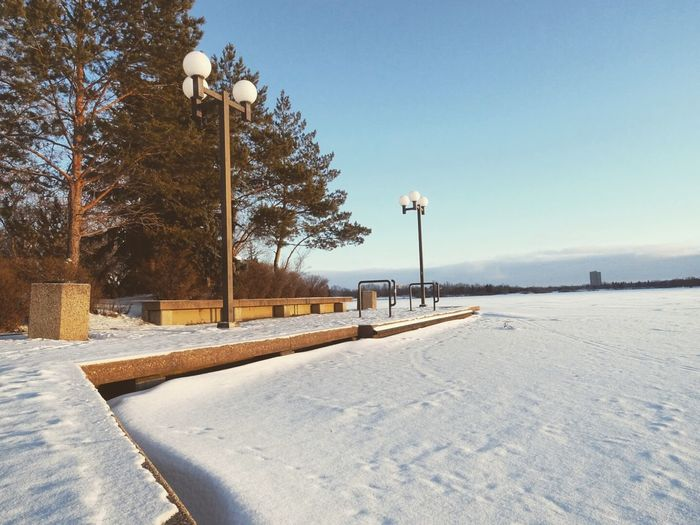 Frozen lake and pier against sky