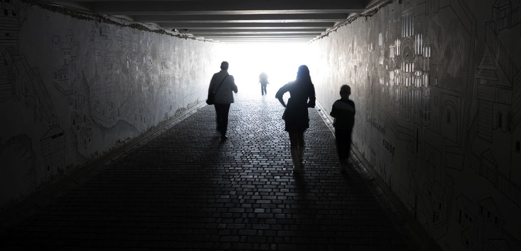 People Walking In Tunnel