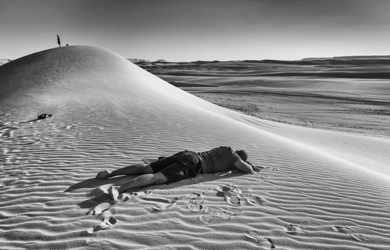 View of man lying on sand dune