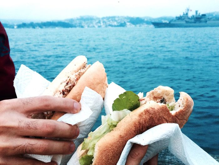Cropped image of hands holding sandwich against sea