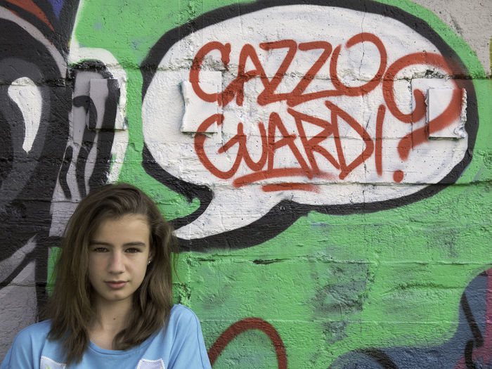 Portrait of teenage girl against graffiti wall