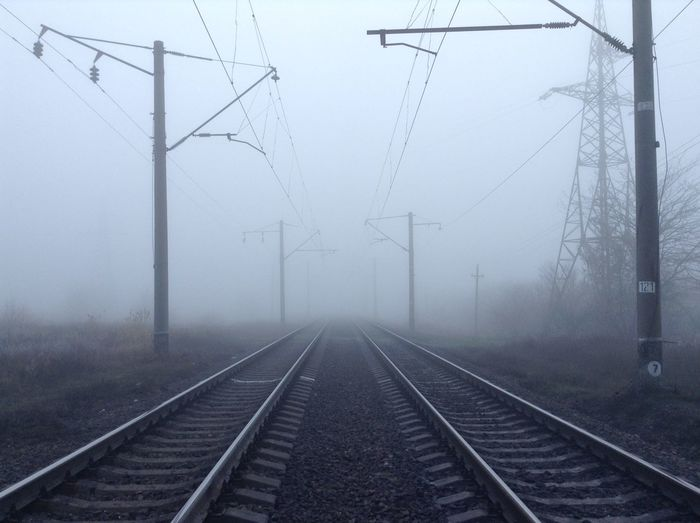 Railroad tracks against sky during foggy weather