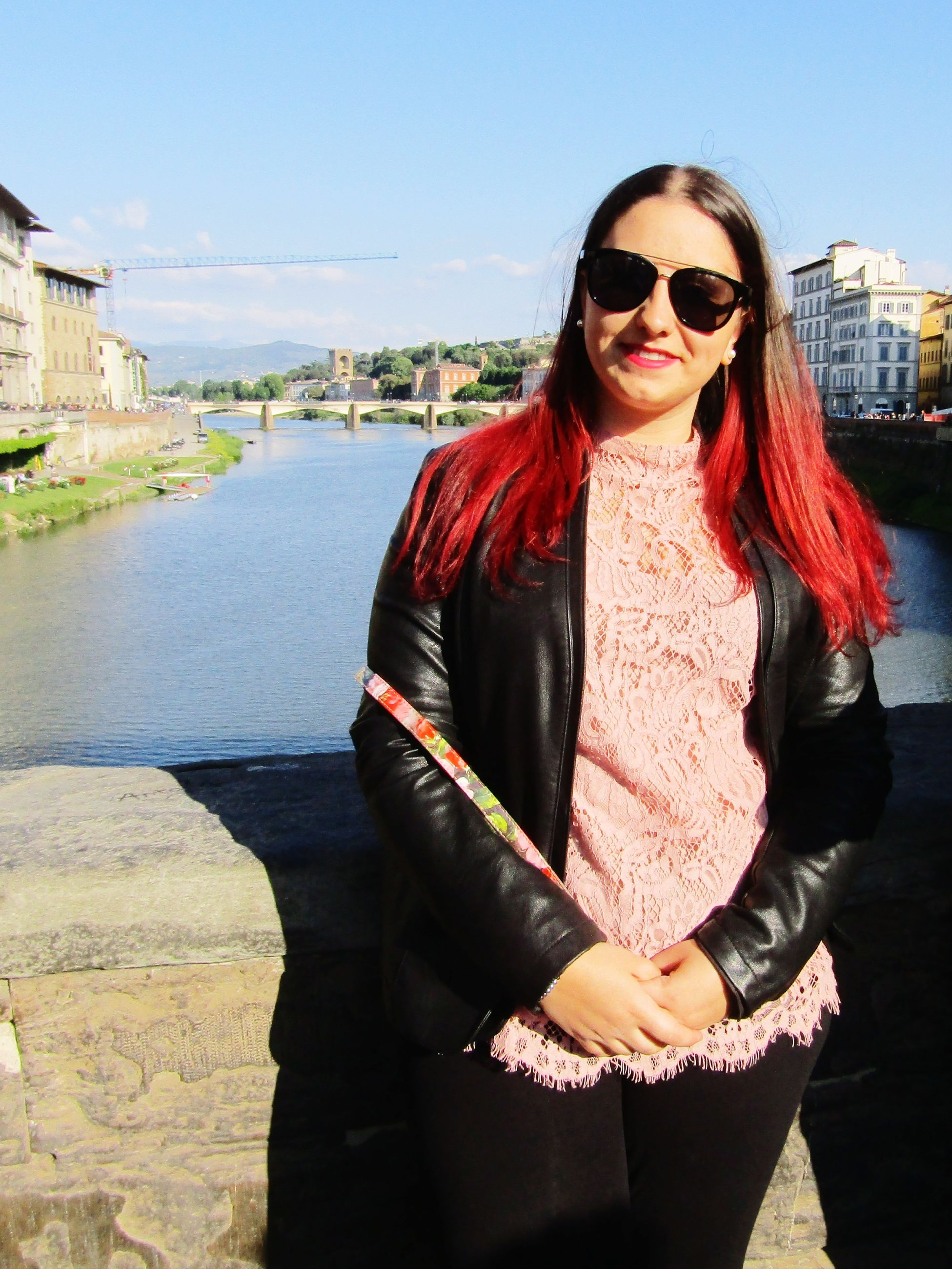 sunglasses, real people, one person, front view, outdoors, young adult, young women, lifestyles, smiling, looking at camera, sunlight, day, portrait, standing, leisure activity, architecture, building exterior, built structure, happiness, sky, retaining wall, water, nature