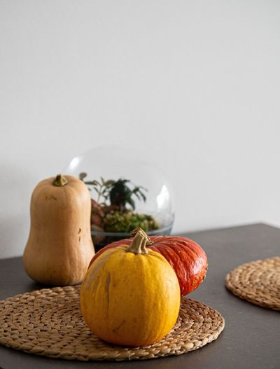 Close-up of pumpkins on table against white background