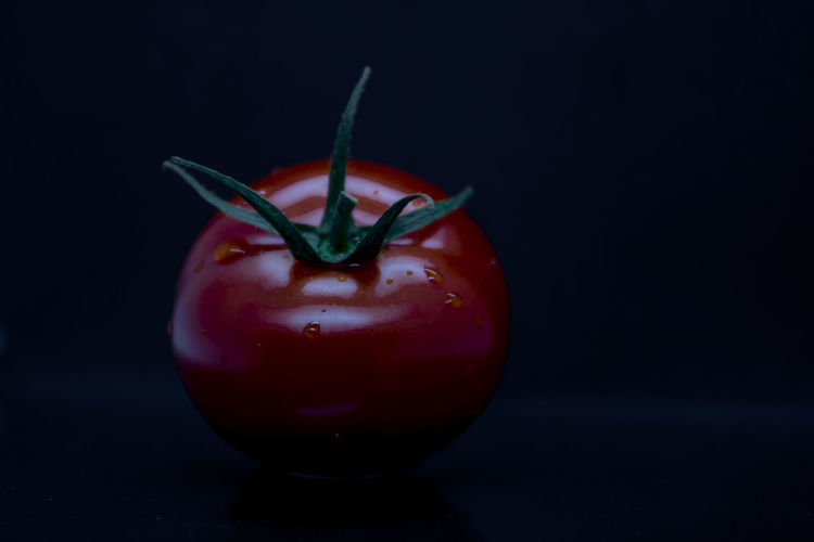 Close-up of red fruit on table against black background