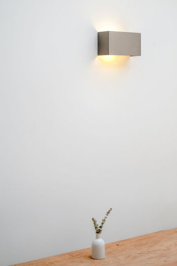 Electric lamp on table against white wall at home