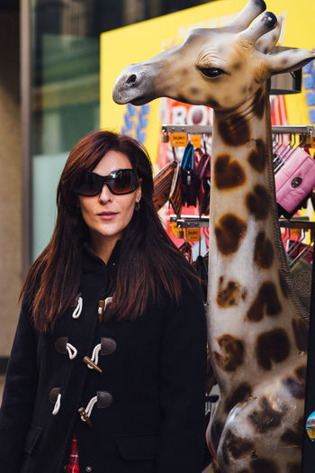 Woman Wearing Sunglasses While Standing By Giraffe Sculpture