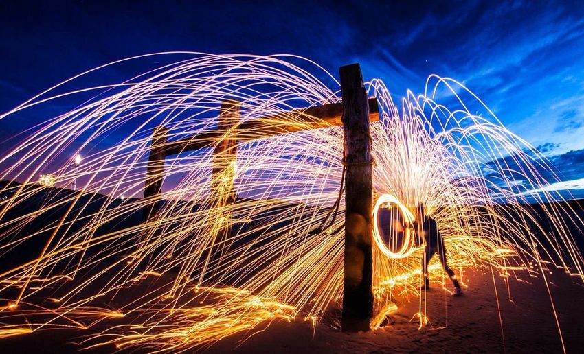 Person spinning wire wool by wooden structure at beach