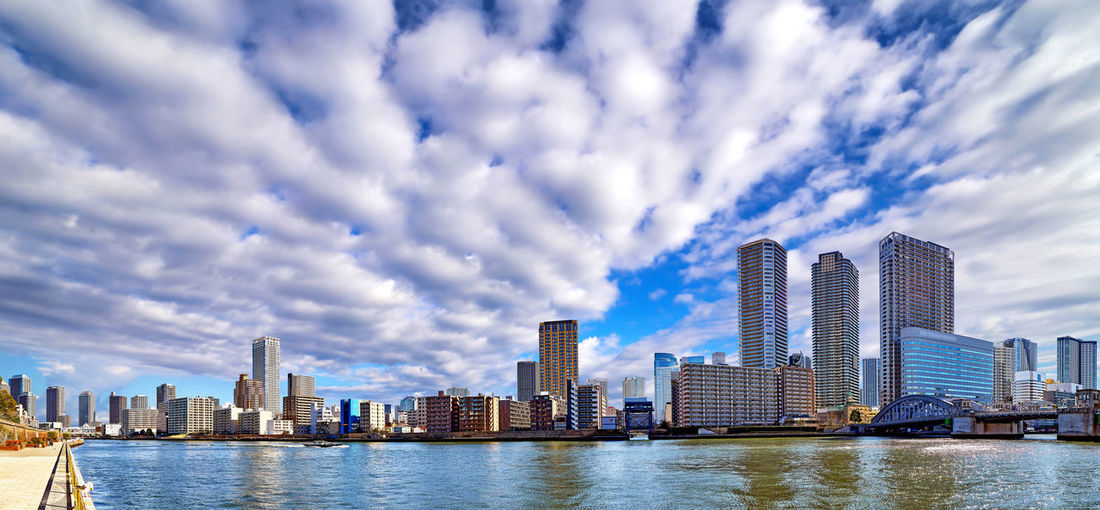 Wide angle sunny panorama of sumida river in tokyo under dramatic cloudy sky