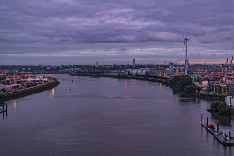 River in city against sky during sunset