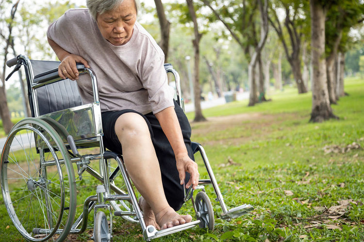 Senior woman sitting on wheelchair at park