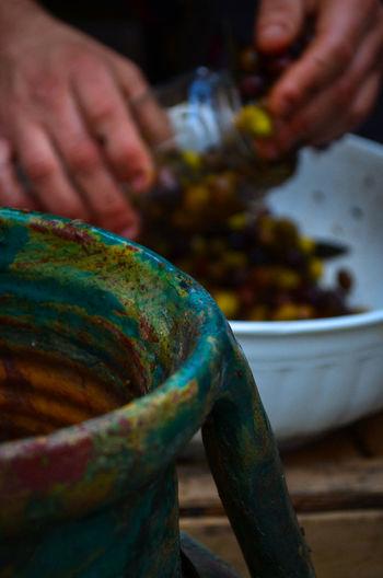 Cropped hands filling olive pickle in jar