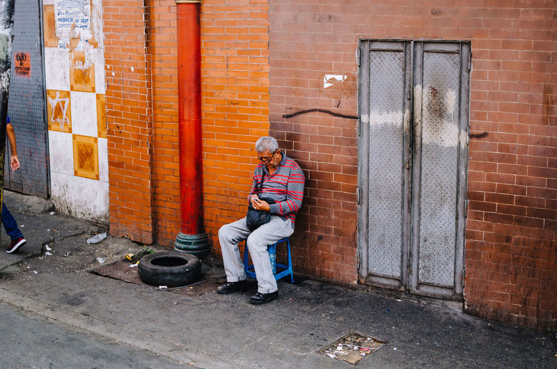 Catia, Caracas. Full Length One Person Real People Leisure Activity Front View Casual Clothing Males  Day Building Exterior Architecture Child Lifestyles Men Built Structure Sitting Boys Entrance Door Outdoors Brick Teenager EyeEm Best Shots EyeEm Selects Street Photography The Art Of Street Photography The Street Photographer - 2019 EyeEm Awards