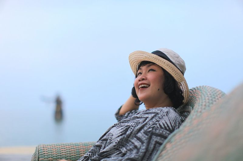 Smiling woman looking away while sitting on sofa against sky
