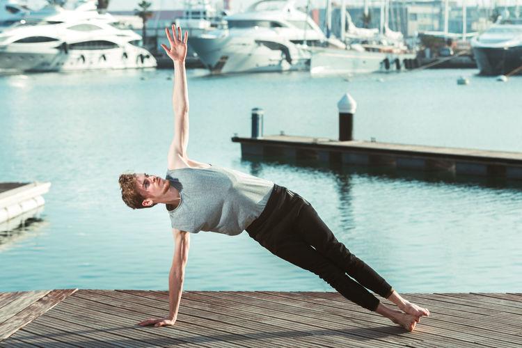 Full length of man doing yoga on pier