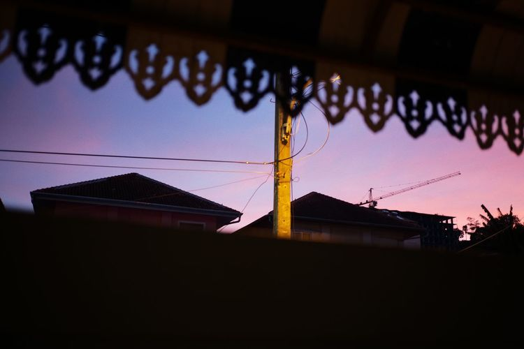 Low angle view of silhouette house against sky at dusk