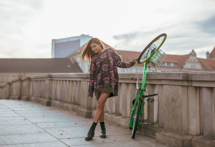 Young Woman Holding Bicycle While Standing Against Railing In City